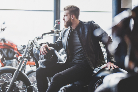 Foto de Handsome bearded man in motorcycle shop. Biker is choosing new vehicle and motorcycle accessories. Cropped image of man sittiing with helmet. Safety driving concept. - Imagen libre de derechos