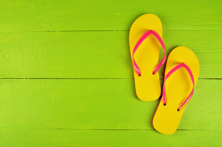 Photo pour Flip Flops Yellow on green wooden background - image libre de droit