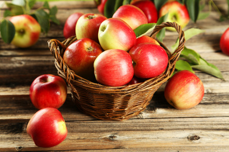 Photo for Apples in basket on brown wooden background - Royalty Free Image