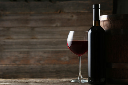 Photo pour Red wine glass with bottle and barrel on grey wooden background - image libre de droit