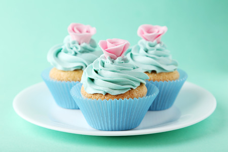 Photo for Tasty cupcake on plate on green background - Royalty Free Image