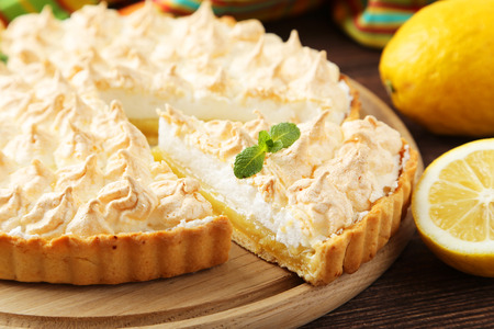 Photo for Lemon meringue pie on cutting board on brown wooden background - Royalty Free Image