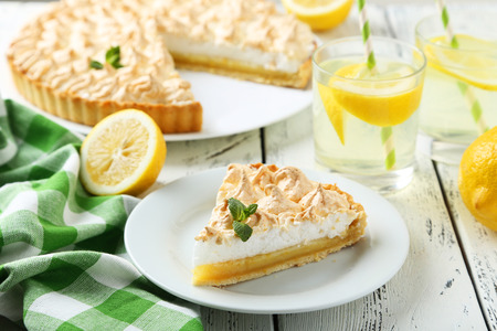 Photo for Lemon meringue pie on plate on white wooden background - Royalty Free Image