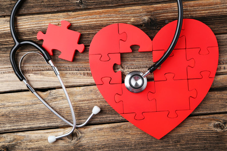 Photo pour Red puzzle heart with stethoscope on brown wooden background - image libre de droit