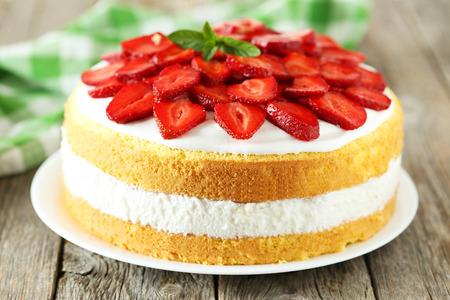 Foto de Sweet cake with strawberries on plate on grey wooden background - Imagen libre de derechos