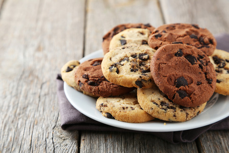 Foto per Chocolate chip cookies on plate on grey wooden background - Immagine Royalty Free