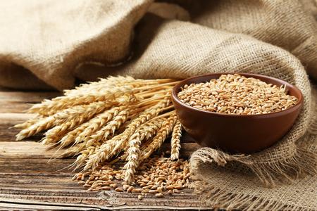 Foto de Ears of wheat and bowl of wheat grains on brown wooden background - Imagen libre de derechos
