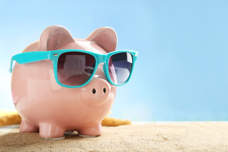 Photo pour Piggy bank with sunglasses on the beach - image libre de droit