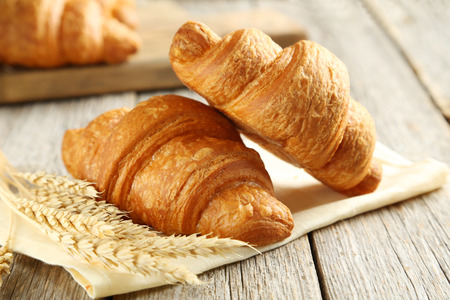 Photo for Tasty croissants with spikelets on grey wooden background - Royalty Free Image