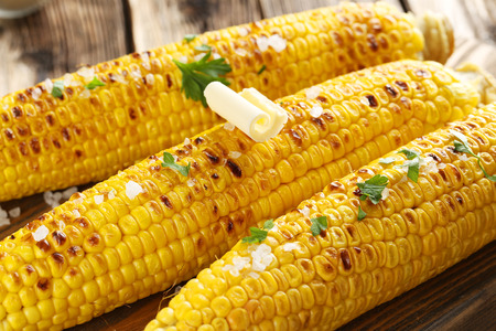 Foto de Fresh tasty grilled corn with butter on brown table - Imagen libre de derechos