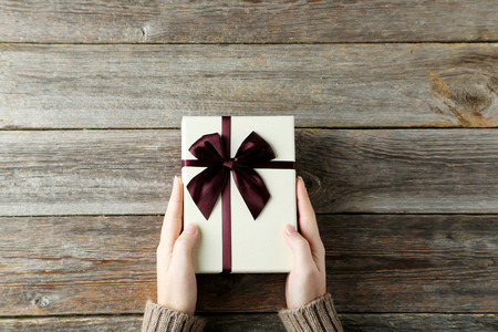 Photo for Female hands holding gift box on grey wooden background - Royalty Free Image