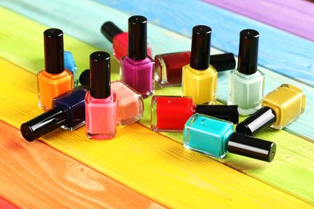 Foto de Bottles of nail polish on a colorful wooden table - Imagen libre de derechos