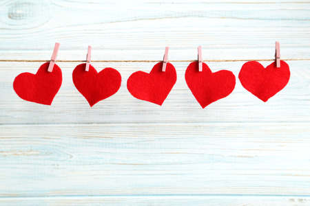 Photo for Love hearts hanging on rope on a blue wooden background - Royalty Free Image
