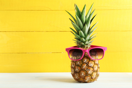 Photo pour Ripe pineapple with sunglasses on a white wooden table - image libre de droit
