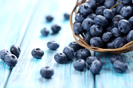 Photo for Tasty blueberries in basket on a blue wooden table - Royalty Free Image