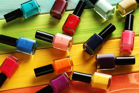 Photo pour Bottles of nail polish on a colorful wooden table - image libre de droit