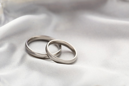 Photo for Silver wedding rings on a white satin - Royalty Free Image