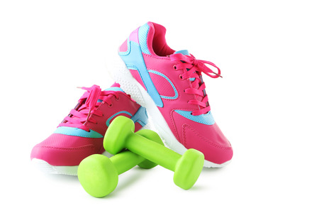 Sport shoes with dumbbells isolated on a white background