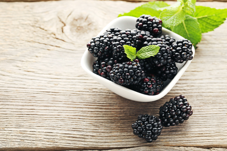 Photo for Ripe and sweet blackberries in bowl on wooden table - Royalty Free Image