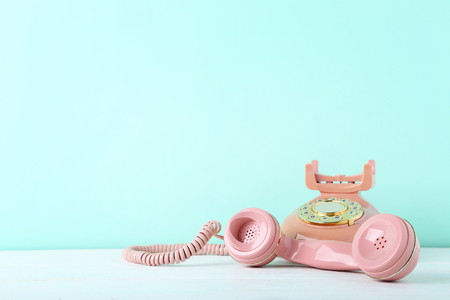 Photo pour Pink retro telephone on white wooden table - image libre de droit