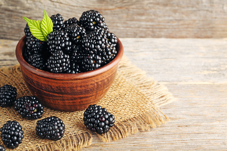 Photo for Ripe blackberries in bowl on wooden table - Royalty Free Image