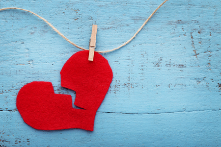 Photo for Broken red heart hanging on rope on blue wooden table - Royalty Free Image