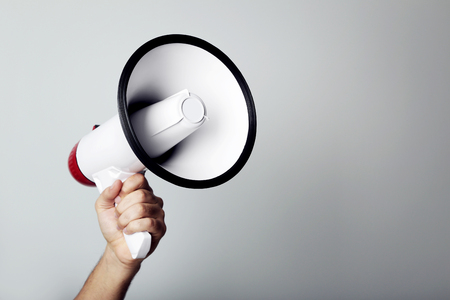 Foto de Female hand holding megaphone on grey background - Imagen libre de derechos