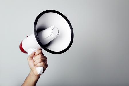 Photo for Female hand holding megaphone on grey background - Royalty Free Image