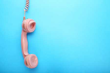 Photo pour Pink telephone handset on blue background - image libre de droit