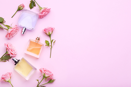 Photo for Perfume bottles with flowers on pink background - Royalty Free Image