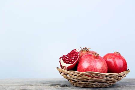 Photo pour Ripe and juicy pomegranate in basket on grey wooden table - image libre de droit