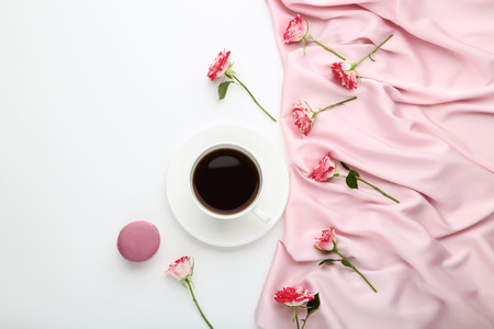 Foto de Rose flowers with cup of coffee and satin fabric on white background - Imagen libre de derechos