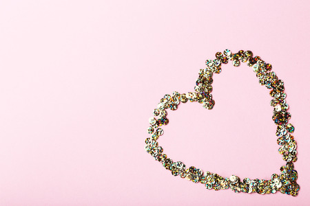 Photo for Round colorful sequins in heart shape on pink background - Royalty Free Image