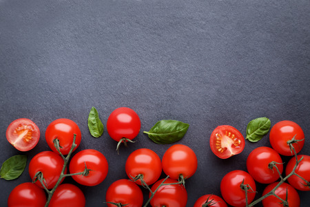 Photo for Cherry tomatoes with basil leafs on black background - Royalty Free Image