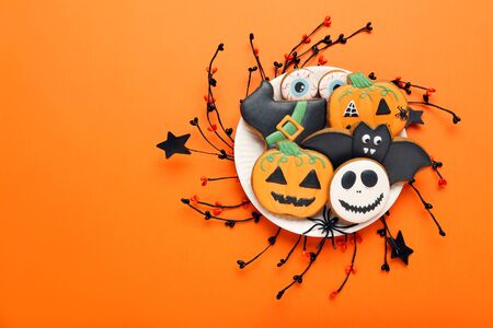 Photo pour Halloween gingerbread cookies in plate on orange background - image libre de droit