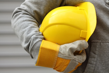 Photo pour Man holding yellow helmet close up - image libre de droit