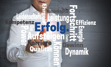 Erfolg (in german Success) Wordcloud touchscreen is operated by man.