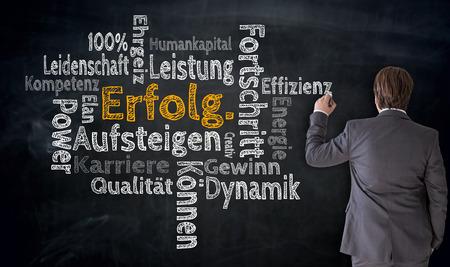 Businessman writes Erfolg, Aufsteigen, Fortschritt (in german success, rising, progress) Cloud on blackboard concept.