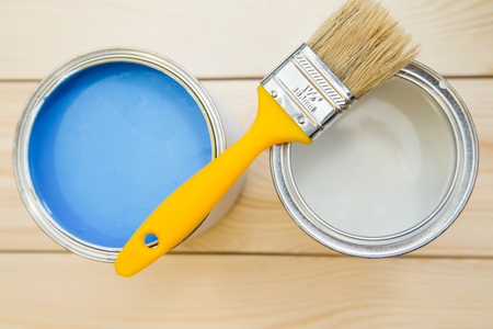 Photo pour Repair in a house. Tin cans of blue and white oil paint with a yellow brush and can of white paint on a light uncolored wooden background. Close up. Top view. Space for your text or pruduct display. - image libre de droit