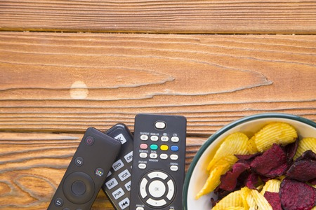 Photo for Weekend, leisure, hobby concept. A wooden background with tv remote controls and a bowl of potato and beetroot chips. Space for your inscription or image. - Royalty Free Image