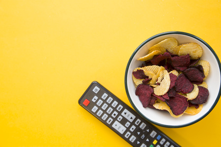 Photo for Weekend, hobby and leisure concept. A one-color yellow background with bowl of potato and beetroot chips and a tv remote control. Space for your text or image. - Royalty Free Image
