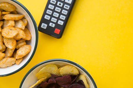 Photo for Entertaining at home. Weekend, hobby and leisure concept. A bowl of salty croutons and potato and beetroot chips and a remote control on a bright one-color yellow background. - Royalty Free Image