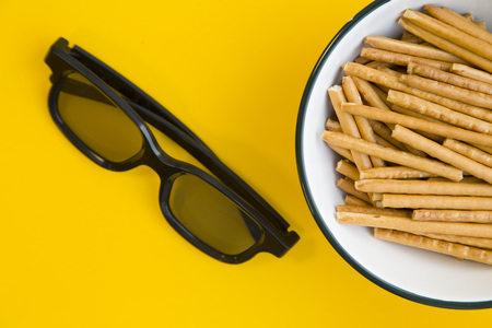 Photo for Weekend at home with tv shows. A bowl of salty bread sticks and a pair of glasses on a bright one-color yellow background. Close up. Space for a text or product display - Royalty Free Image