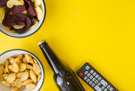 Photo for Watching sport channel with friends. Two bowls with crunchy snacks, a bottle of cold stout beer and a remote control on a bright one-color yellow background. Space for a text or product display - Royalty Free Image