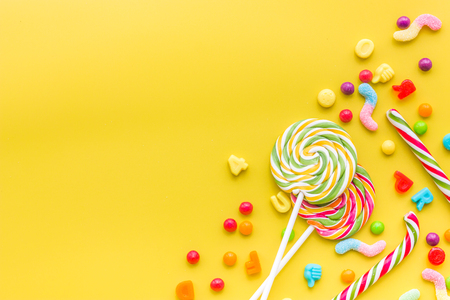 Photo for Sweets for birthday including lollipop and drops on yellow background top view copyspace. - Royalty Free Image