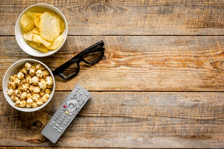 Photo for TV remote control, snacks, beer for whatchig film on wooden desk background top view space for text - Royalty Free Image