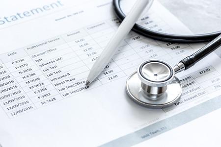Foto de billing statement for for medical service in doctor's office on stone desk background - Imagen libre de derechos