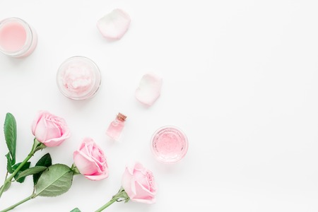 Photo pour cosmetic set with rose blossom and body cream on white desk background top view mock-up - image libre de droit
