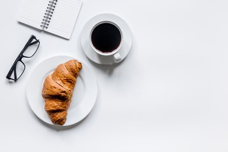 Foto de Businessman morning with notebook, cup of coffee and croissant on wooden table background top view mockup - Imagen libre de derechos