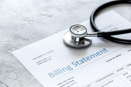 Foto de health care costs with billing statement, stethoscope on stone table - Imagen libre de derechos